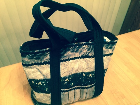 "ITEM 010 (view 1 of 2) - Silver and black quilted tote bag made by Barbie Woolley. 15""x12""x4"" with 2 pockets, a water bottle holder, and magnetic closure."