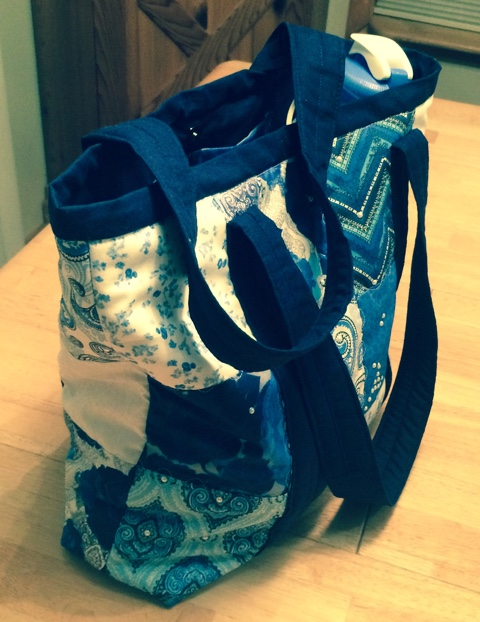 "ITEM 012 (view 2 of 2) - Multi-blue and white quilted tote bag with pearl accents made by Barbie Woolley. 15""x13""x4"" with 2 inside pockets plus water bottle holder and magnetic closure."
